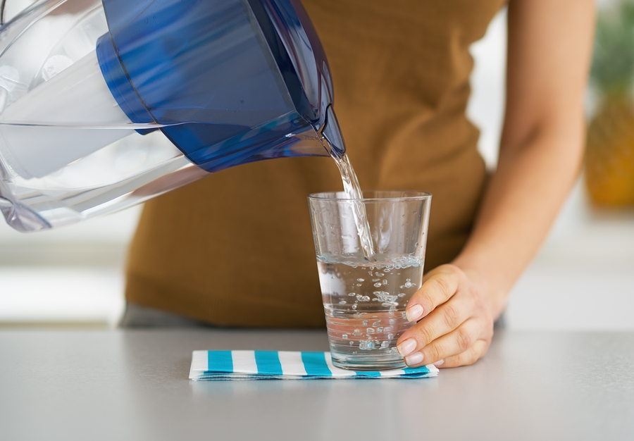 Closeup On Housewife Pouring Water Into Glass From Water Filter