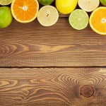 Citrus fruits. Oranges, limes and lemons. Over wooden table back